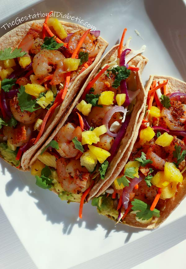 Overhead view of 3 shrimp tacos with bacon and pineapple