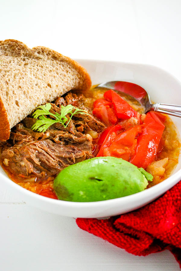 Close up of bowl with ropa vieja, avocado, sliced red bell pepper and bread slice