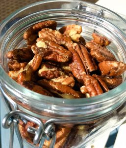 closeup view of candied pecans in glass jar
