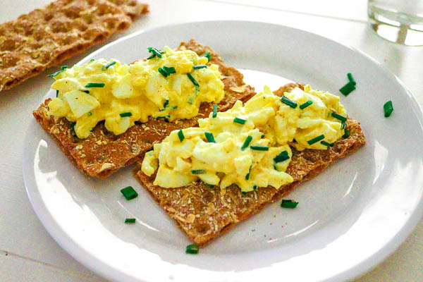 egg salad with chives on long wheat crackers, on a plate