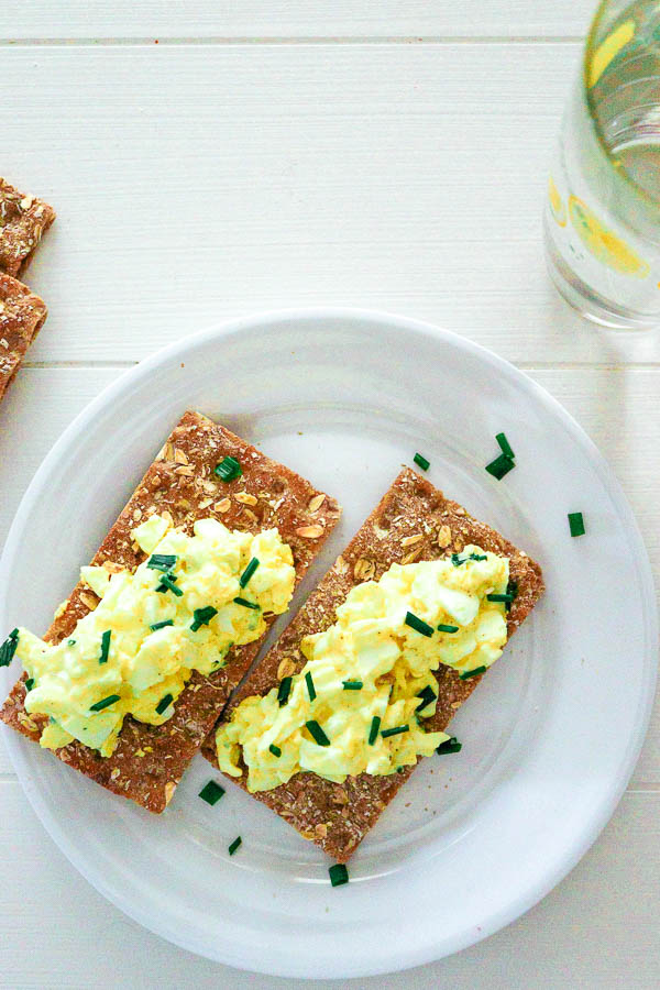 overhead view of egg salad with chives on long wheat crackers